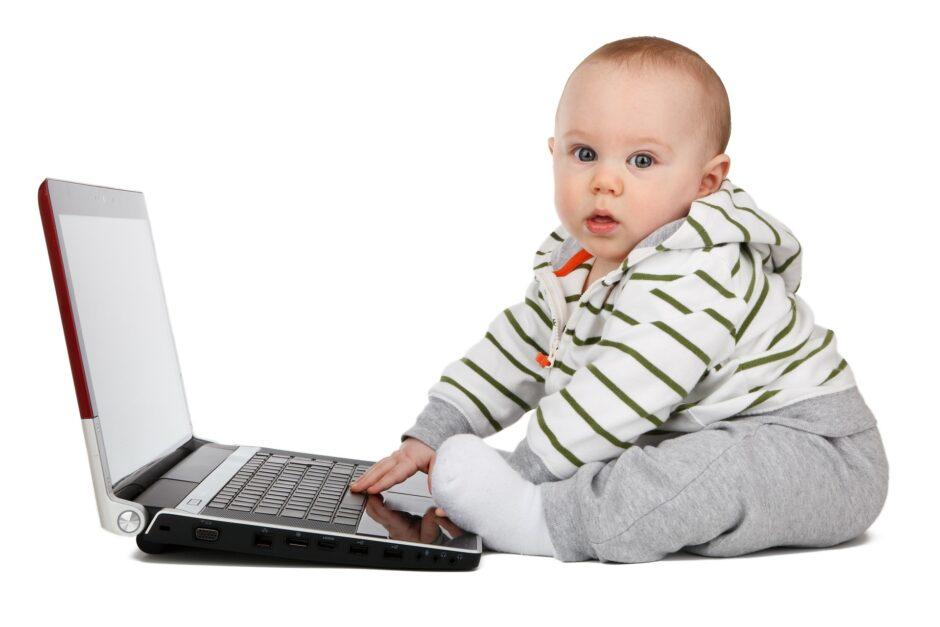 ノートパソコンを触って横を観てる赤ちゃん