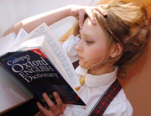女の子が片腕で頭を抱えて寝ながら本を見ている