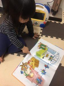 小さな男の子が本を指さしています