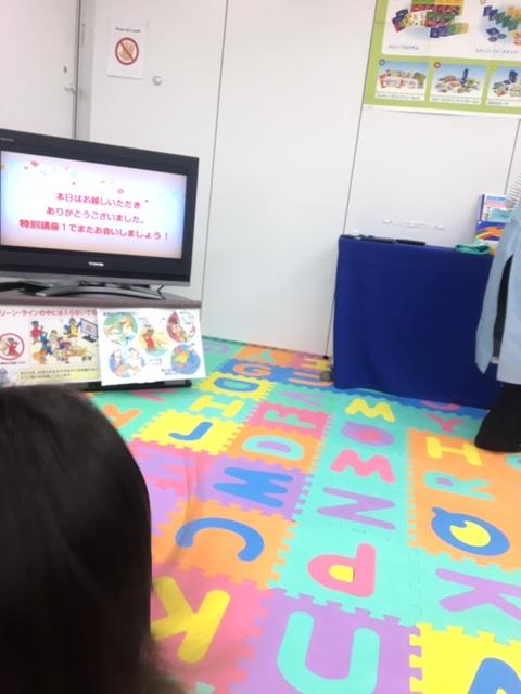 男の子の向こうに小さなテレビと机の角がみえます