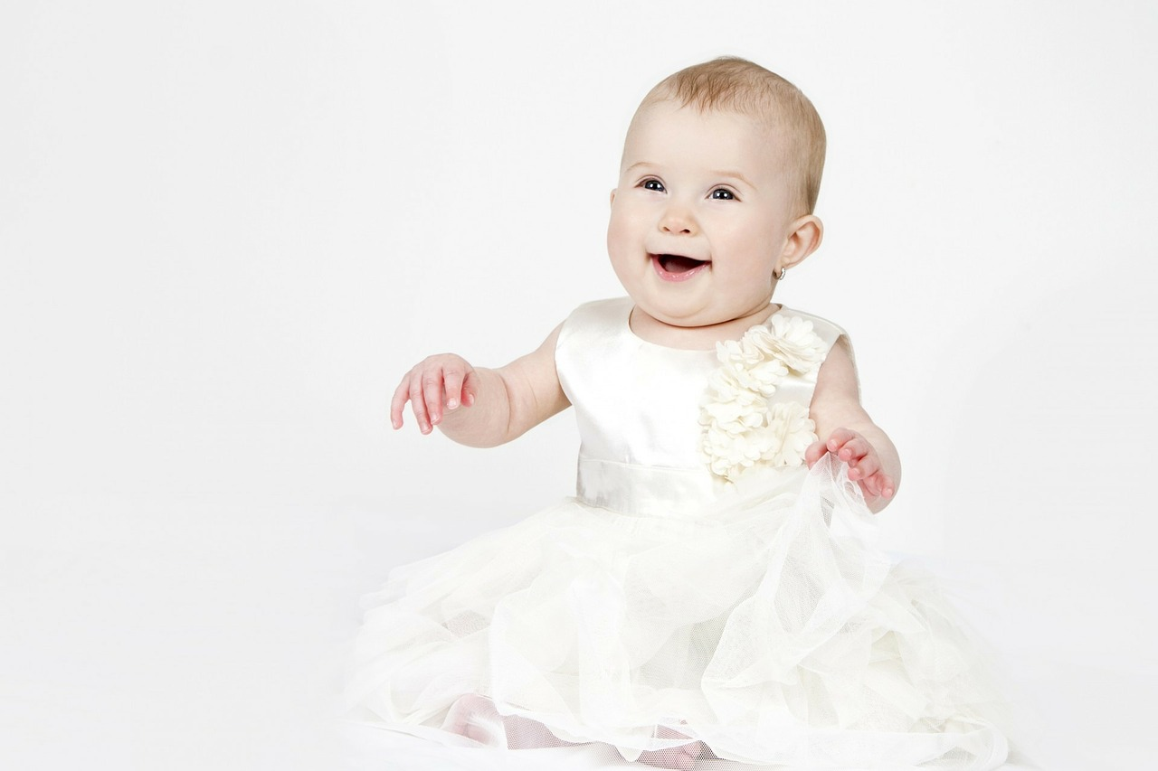 白いドレスをきているお座りできるようになった赤ちゃん