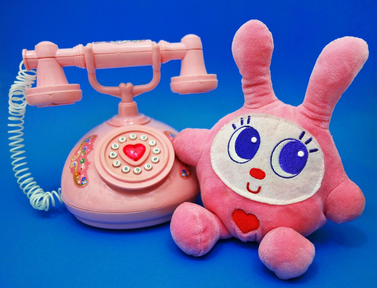 ピンクの電話の隣にウサギのぬいぐるみがある